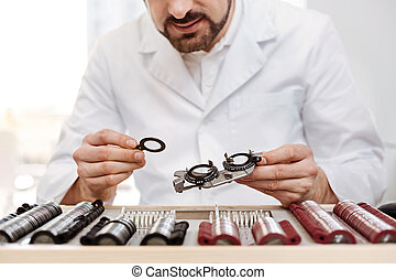 Charming scrupulous ophthalmologist picking right lenses
