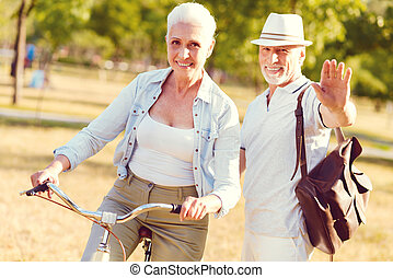 Charming senior couple spending active day in local park