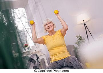 Charming senior woman smiling and lifting up dumbbells