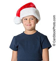 Charming seven-year boy in Santa Claus hat smiles