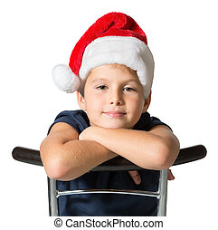 Charming seven year old boy in red Santa hat smiles -...