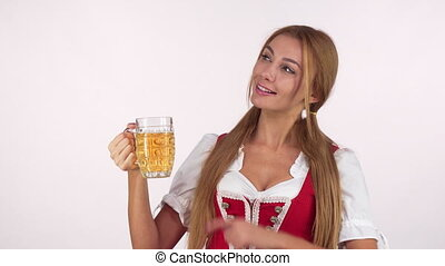 Charming sexy Bavarian woman holding beer mug pointing at the copy space