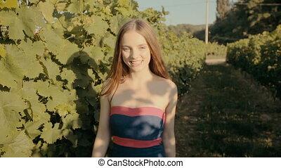 Charming slim girl in a strapless dress walks along the vineyards