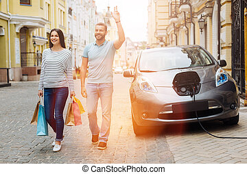 Charming smiling couple greeting someone on the street