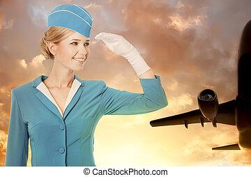Charming Stewardess Dressed In Blue Uniform On Sky Background