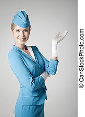 Charming Stewardess Dressed In Blue Uniform Pointing On Gray...