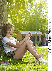 Charming Student Girl Sitting on Green Grass