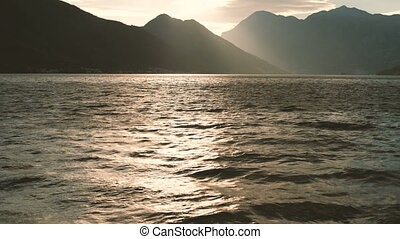 Charming sunset on a calm sea with high mountains horizon.