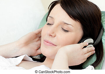 Charming teen girl listening music lying on a sofa