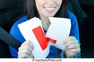 Charming teen girl sitting in her car tearing a L-sign after...