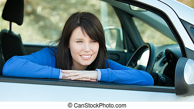 Charming teen girl smiling at the camera sitting in her car