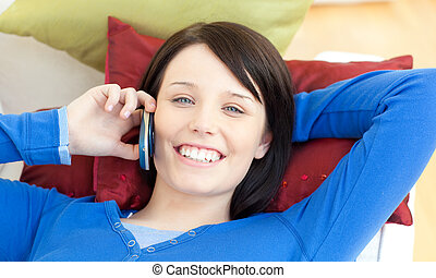 Charming teen girl talking on phone lying on a sofa