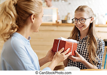 Charming teenage girl being happy to get a present