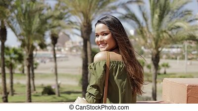 Charming traveler posing in resort - Back view of young...