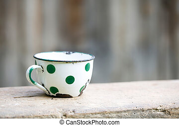Charming vintage dotted metal cup, covered in decorated enamel, rusty on the edges. Home decoration, old times, retro kitchen concept.