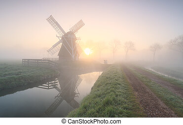 windmill in dense fog at sunrise
