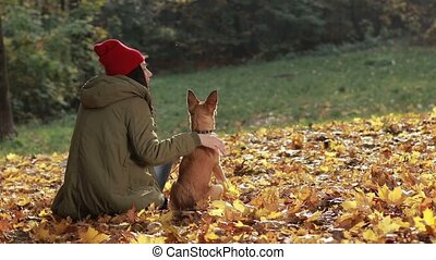 Charming woman and her dog posing in autumn park