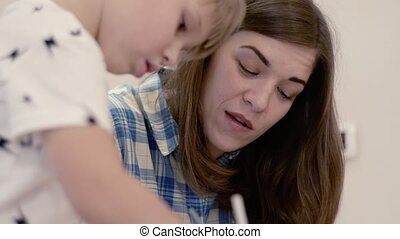 Charming Woman And Little Boy Doing Homework