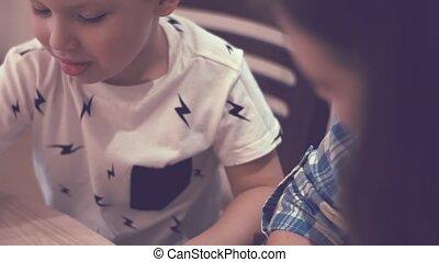 Charming Woman And Little Boy Doing Homework