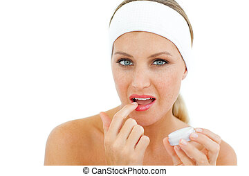 Charming woman applying lip balm isolated on a white...