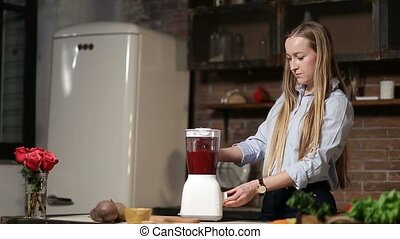 Charming woman blending beet smoothie with blender