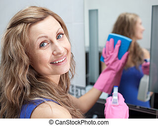 Charming woman cleaning a bathroom\'s mirror with a sponge...