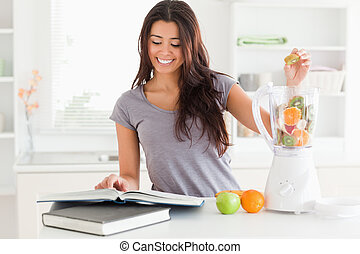 Charming woman consulting a notebook while filling a blender...