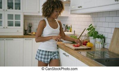 Charming woman dancing while preparing food