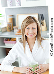 Charming woman drinking a cup of coffee in the kitchen