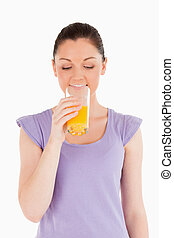 Charming woman drinking a glass of orange juice while standing