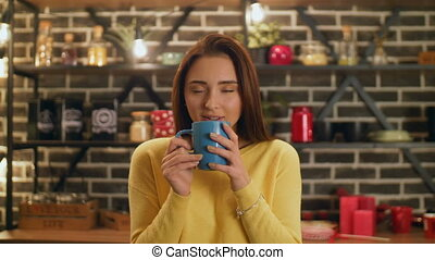 Charming woman enjoying aroma of coffee in kitchen -...