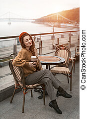 Charming woman enjoying her cup of coffee sitting in a spring outdoor cafe. French woman in red beret with background of urban city. Parisian woman with coffee mug on city street in evening.