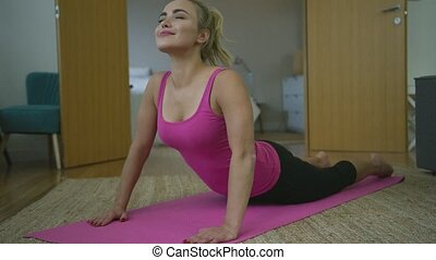 Charming woman exercising on stretching mat
