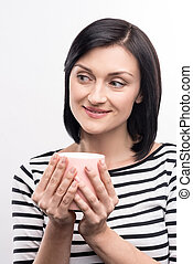 Charming woman holding a cup of coffee