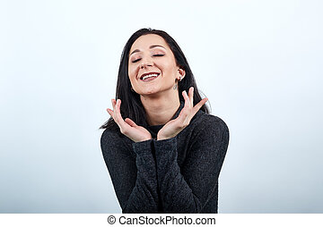 Charming woman holding hands over head, smiling, looking pretty