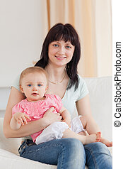 Charming woman holding her baby in her arms while sitting on a sofa in the living room