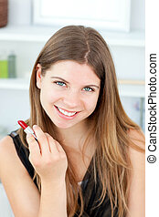 Charming woman holding lipstick in the camera in a bathroom