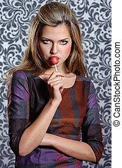 charming woman holding lollipop