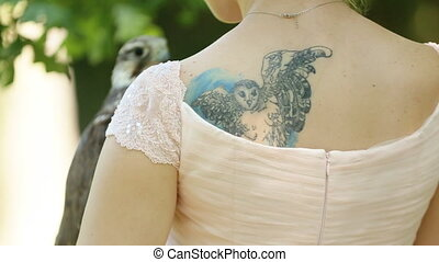Charming woman in a pink dress with owl tattoo holding a falcon on arm