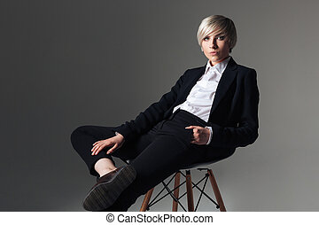 Charming woman in fashion cloth sitting on the chair