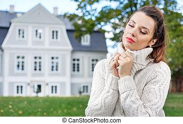 Charming woman in her autumn garden