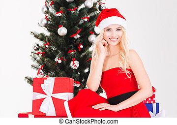 Charming woman in santa claus hat sitting near Christmas tree
