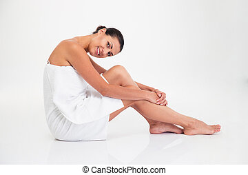 Charming woman in towel sitting on the floor