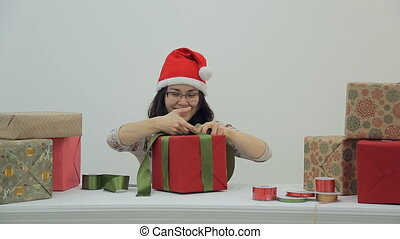 Charming woman is tying ribbon on holiday gift.