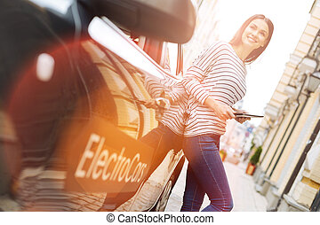 Charming woman leaning on her car while holding tablet