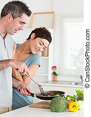 Charming Woman looking into a pan her husband is holding
