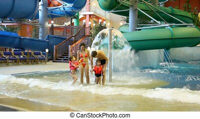 Charming woman , man and children fool near fountain in pool in water park