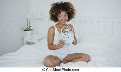 Charming woman posing on bed with clock - Romantic young...