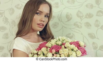 Charming woman posing with a bouquet of roses