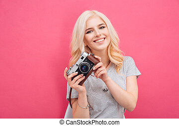 Charming woman posing with photo camera over pink background